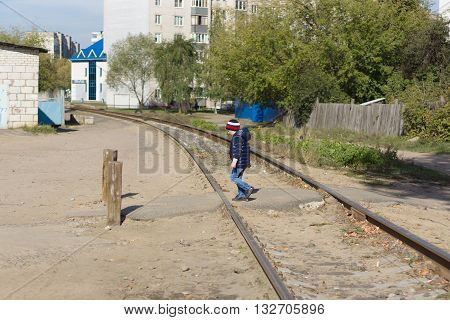 the boy transfers the railway tracks located in the city