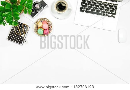 Creative feminine workplace. Coffee macaroon cookies laptop computer and green plant on white table background