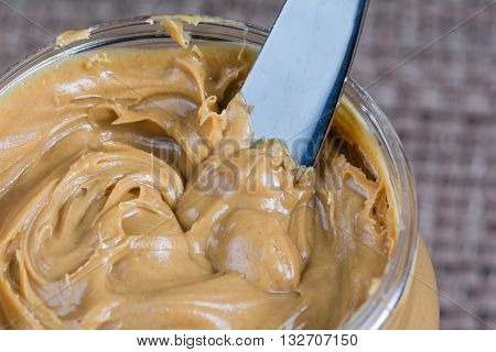 Macro close up of butter knife dipped into creamy peanut butter