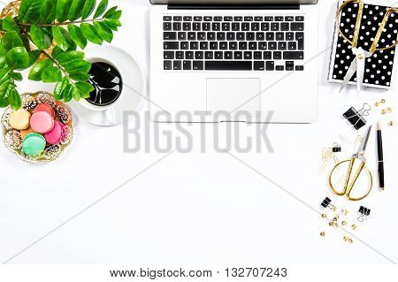 Feminine workplace. Coffee macaroon cookies office supplies laptop computer and green plant on white table background. Top view. Flat lay