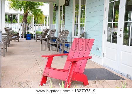 A lone red chair on a big porch