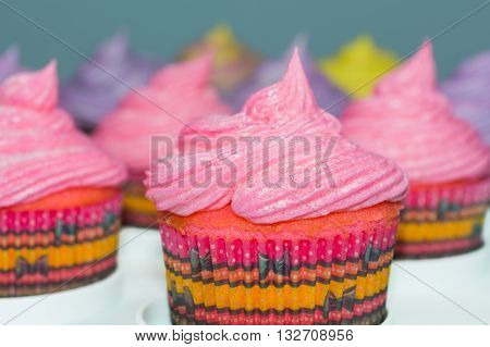 Frosted cupcakes with selective focus on front cupcake with pink frosting