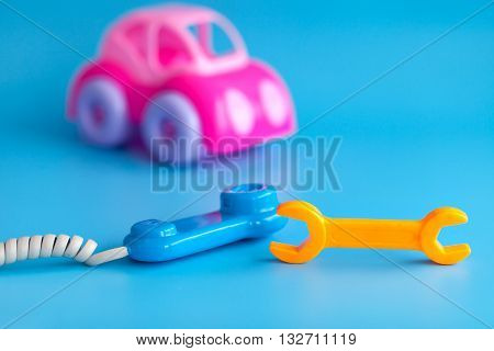Pink toy car made of plastic on a blue background. Toy wrench orange and handset. Playing in car repairs. Call mechanic and repair the machine. Copy space.