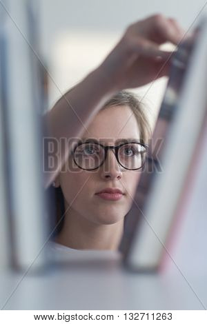 portrait of smart looking famale student girl  in collage school library,  selecting book to read from bookshelf