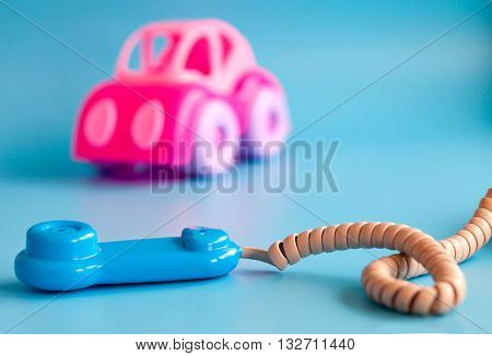 Pink toy car made of plastic on a blue background. Plastic toy phone. Playing in car repairs. Call mechanic and repair the machine. Copy space.