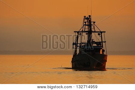 Shrimping boat silhouetted against sunset sky on the ocean.