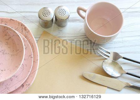 Menu planning. Vintage pink dinnerware overhead view on marble with dinnerware