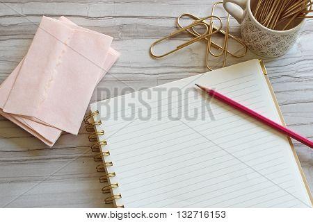 Over head desktop pink envelopes, notebook, pencil, gold paperclips