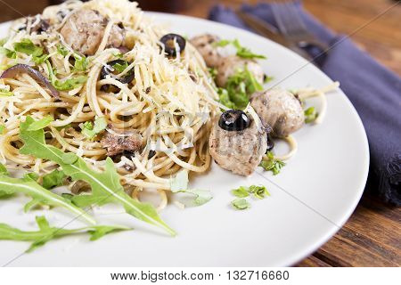 Pasta and meatballs with anchovies and olives. Top view
