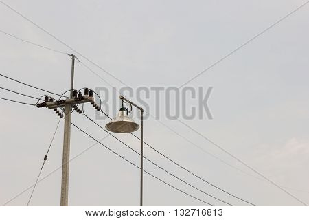 electricity post and lamp on a background of the sky.