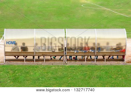 Soccer Players And Staff Sit On Bench Beside The Soccer Field (home Team)