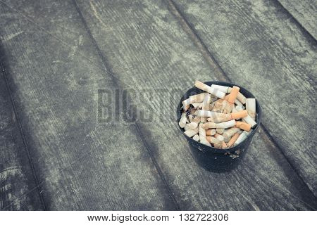 Cigarette in outdoors ashtray with sand on wooden floor process in vintage style