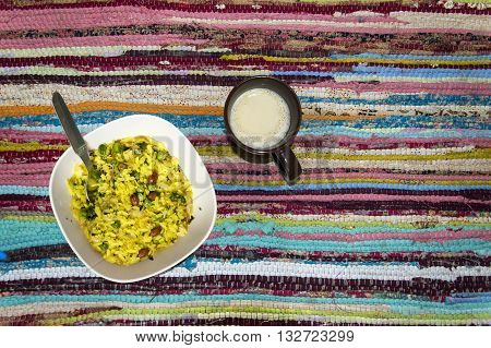Bowl of poha(Flattened rice/beaten rice/Pounded paddy) and a mug of coffee on colorful rug, top view.