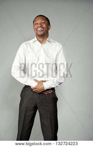 An attractive and happy African American boy wearing a white button down and black slacks on a gray background in a studio setting acting funny.