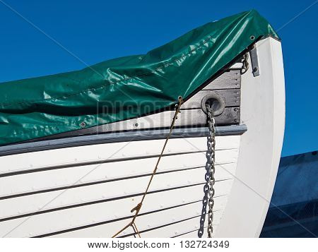 Prow of a small white wooden boat with clear blue sky background