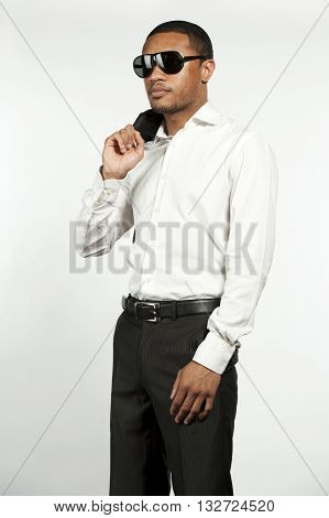 A young chic black male wearing sunglasses, white button down shirt with black pants with sports jacket over his shoulder in a studio setting on a white background.