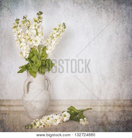 A vase of ivory stocks over white background. Textured to look like an aged photo