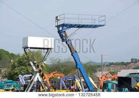 Two platforms high up among the construction equipment.