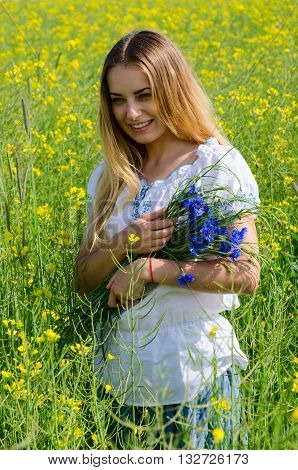 Beautiful smiling girl with a bouquet of cornflowers on a flowering rapeseed field
