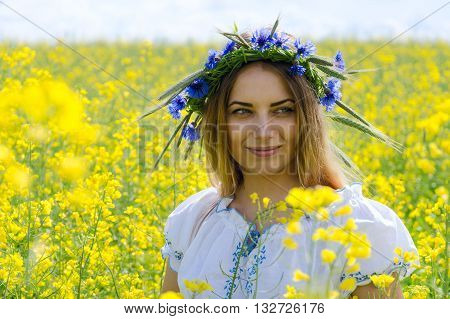 Portrait of beautiful girl in wreath of cornflowers on flowering rapeseed field