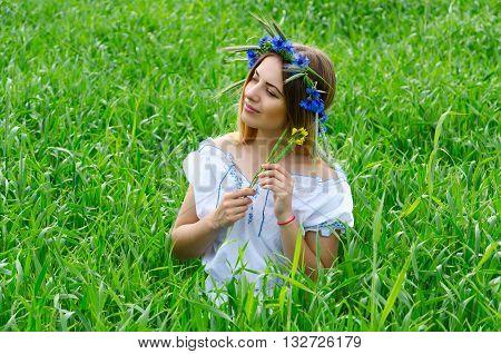 Pretty girl in wreath from cornflowers sits in field among green wheat ears