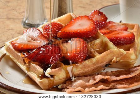 Pouring maple syrup onto Belgian Waffles close up