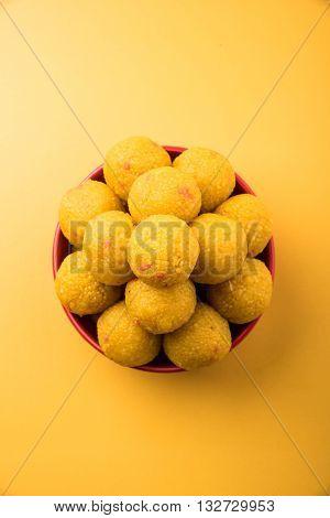 pile of indian sweet bundi laddu or motichur laddu stacked in a red bowl, selective focus