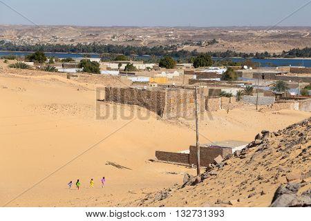 Kids running on sandy desert at Nubian village, Egypt.