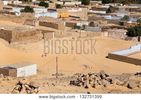 Kids playing on sandy desert at Nubian village, Egypt.