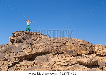 Tourist with turban and sunglasses spreading arms on big rock in desert, Egypt.