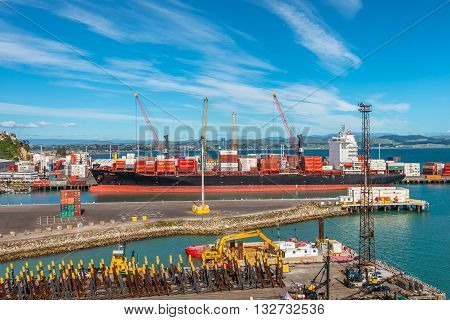 Wellington New Zealand - November 18 2014: Docked container ship Cap Coral being loaded at a working port on Wellington New Zealand. Metal constructions in the foreground ready for export.