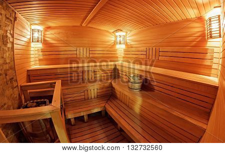 Light wooden sauna with bench and bucket
