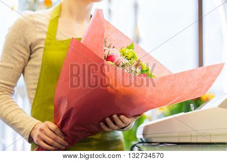 people, business, sale and floristry concept - close up of florist woman holding bunch of flowers wrapped into paper at flower shop