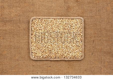 Frame made of rope with pearl barley grains on sackcloth with place for your creativity
