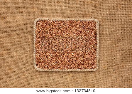 Frame made of rope with buckwheat grains on sackcloth with place for your creativity