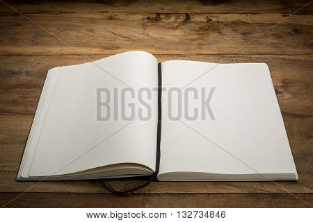 Open book on dark wooden desk blank with copy-space closeup.