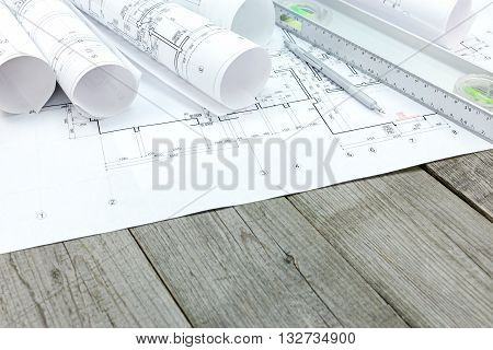Floor Plan Drawings With Blueprint Rolls And Spirit Level On Wooden Desk