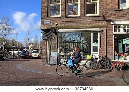 AMSTERDAM, NETHERLANDS - MAY 3, 2016: Local woman on bicycle in historical center in Amsterdam, the Netherlands. Bicycles outnumber the people in Amsterdam: 760000 citizens and nearly a million bikes.