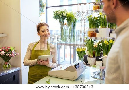 people, shopping, sale, floristry and consumerism concept - happy smiling florist woman with tablet pc computer and man or customer at flower shop