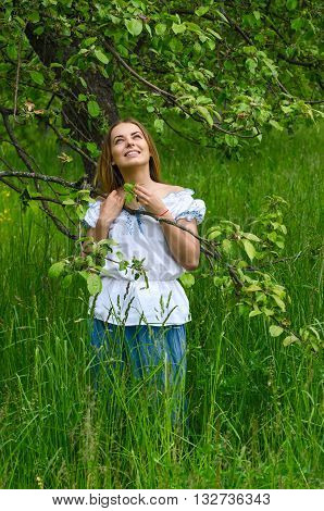 Young beautiful woman in the apple orchard