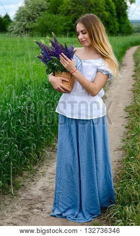 Beautiful girl with a basket of wild flowers on a rural road near green field