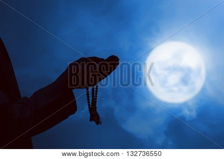 Image of silhouette man praying with full moon background