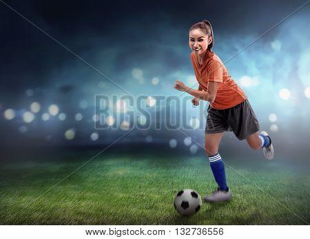 Female Football Player Dribbling Ball