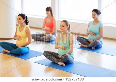 pregnancy, sport, fitness, people and healthy lifestyle concept - group of happy pregnant women exercising yoga and and meditating in lotus pose in gym