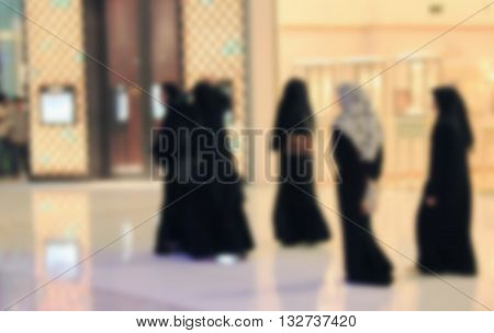 Arab woman walking through the mall blurred for background