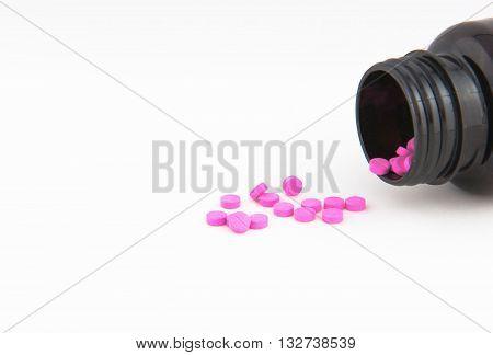 Pink drug tablets in bottles health background