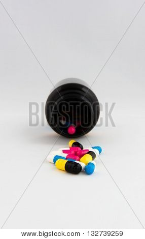 Capsules drug tablets in bottles background colorful