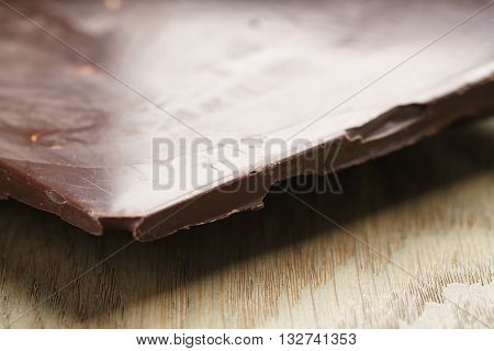 whole homemade bar of chocolate with cashew nuts, on wooden board shalow focus