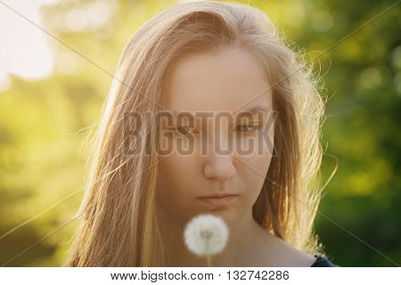 teen girl ready to blow dandelion to the camera, focus on girl