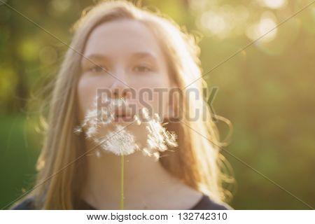 teen girl blowing dandelion to the camera, focus on dandelion